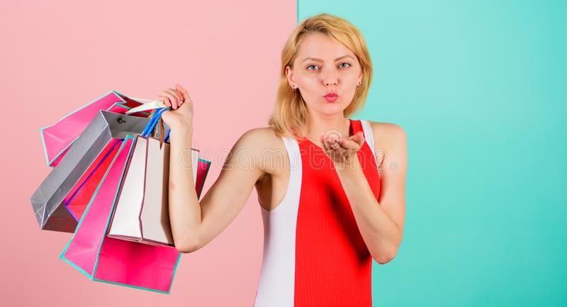 Tips to shop sales successfully. Girl enjoy shopping or just got birthday gifts. Woman red dress hold bunch shopping. Bags blue pink background. Buy everything royalty free stock photo