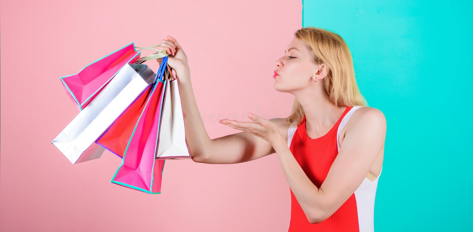 Tips to shop sales successfully. Woman red dress hold bunch shopping bags blue pink background. Girl enjoy shopping or. Just got birthday gifts. Buy everything royalty free stock photo