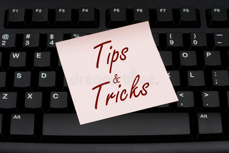 Tips and Tricks. Computer keyboard with a pink sticky note with text tips and tricks, Tips and Tricks