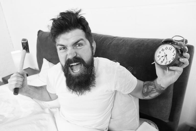 Tips for waking up early. Tips for becoming an early riser. Man bearded hipster sleepy face in bed with alarm clock. Problem with early morning awakening. Get royalty free stock photo