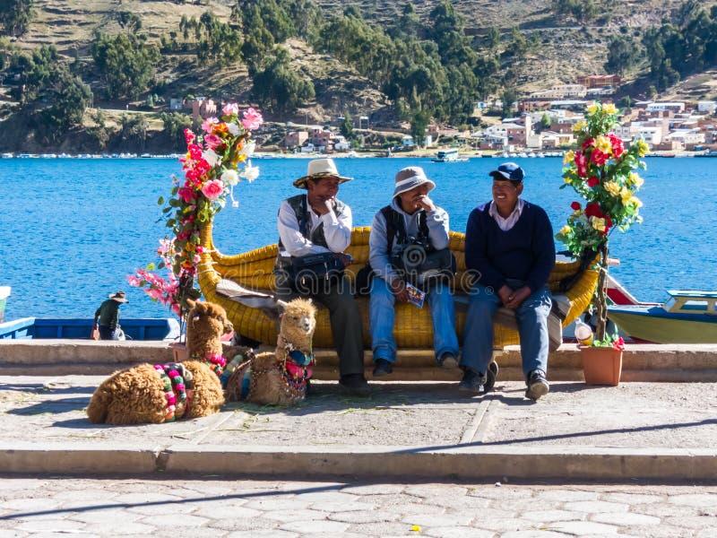 Tiquina, Bolivia - 7 dicembre 2011: Tre uomini che si siedono su un banco immagine stock