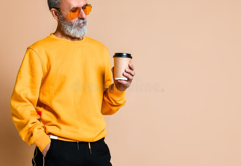 Tiré d'un aîné joyeux tenant une tasse de café blanc et regardant la caméra images stock