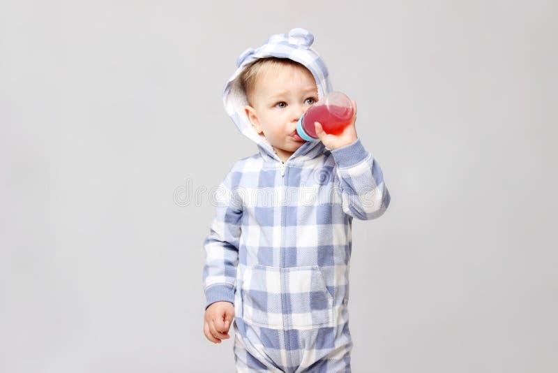 Tiré d'un petit bébé garçon buvant d'une tasse sippy photos libres de droits
