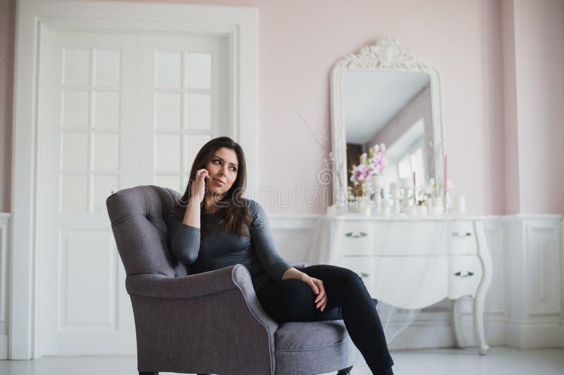 Tiré d'une femme occasionnelle parlant avec quelqu'un à son téléphone portable tout en se reposant sur le fauteuil à la maison photographie stock