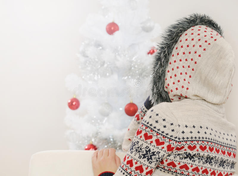 Tiré d'une jeune femme de l'observation arrière sur l'arbre de Noël photos stock