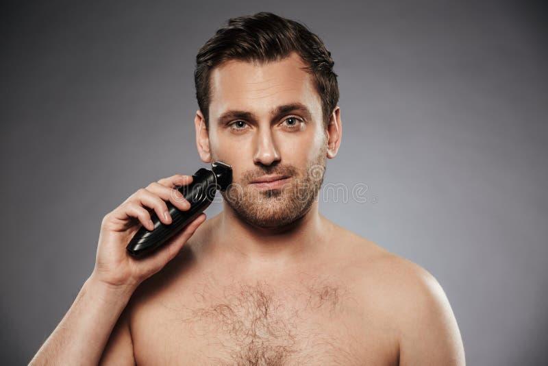 Tiré de l'homme bel rasant son visage avec le rasoir électrique, maki image libre de droits