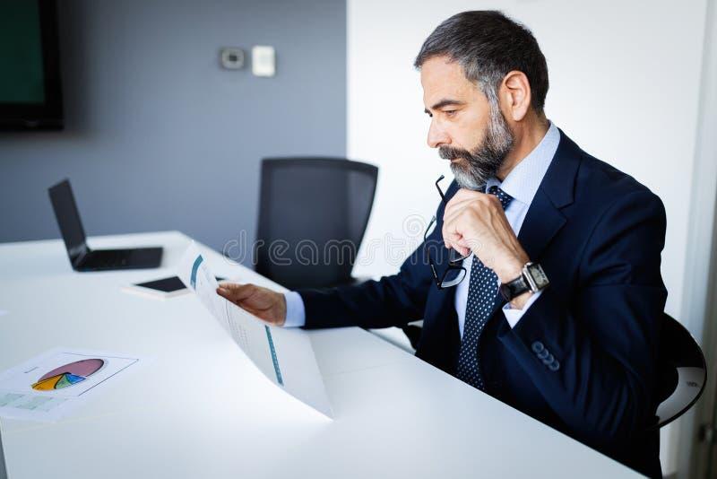 Tiré de l'homme d'affaires financier de pensée de conseiller travaillant dans le bureau photos stock