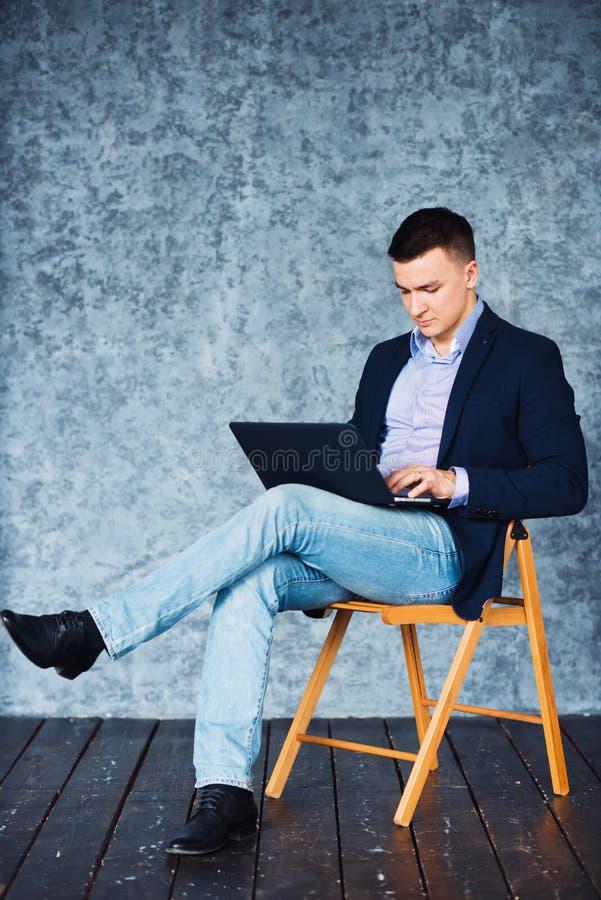 Tiré de l'homme d'affaires s'asseyant sur la chaise et travaillant sur son ordinateur portable photo stock