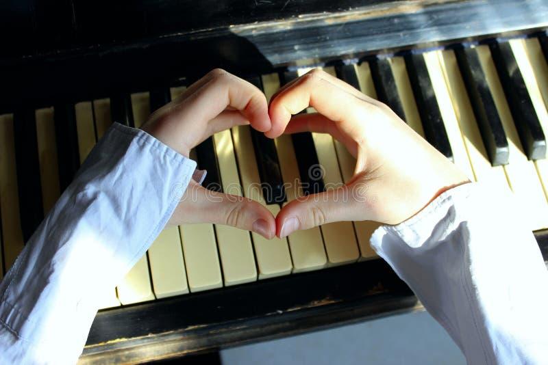 Tiré des mains femelles non identifiables faisant une forme de coeur au-dessus d'un piano photos libres de droits