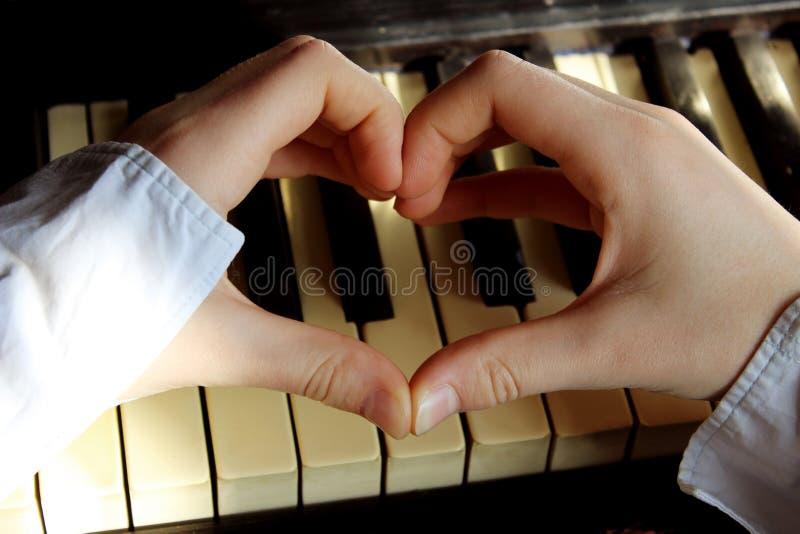 Tiré des mains femelles non identifiables faisant une forme de coeur au-dessus d'un piano photographie stock