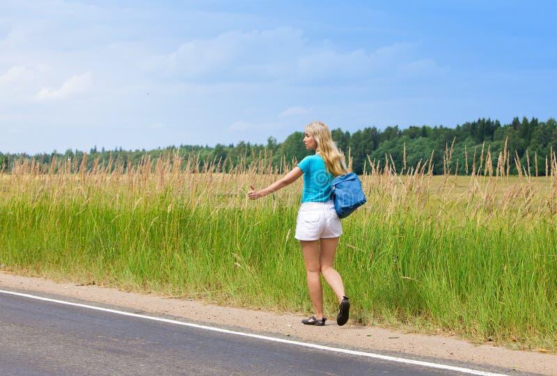Tirón hermoso de la mujer joven que va de excursión en auto-stop imagen de archivo libre de regalías