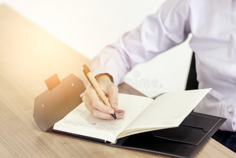 Tir étroit de main écrivant quelque chose à l'ordre du jour photos stock