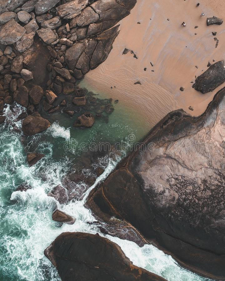 Tir aérien d'un beau canal de l'eau avec des roches et des personnes autour photo libre de droits