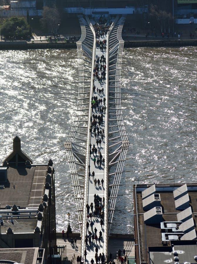 Tir aérien d'un pont moderne au-dessus d'un lac avec le croisement de personnes images stock