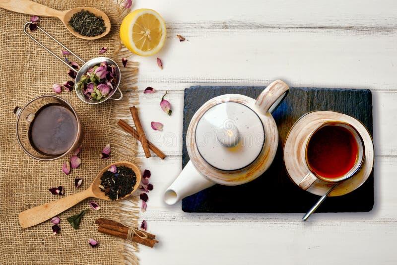 Tir aérien d'une tasse de thé complètement de pot de thé et blanc noir de thé avec des épices et des articles photo stock