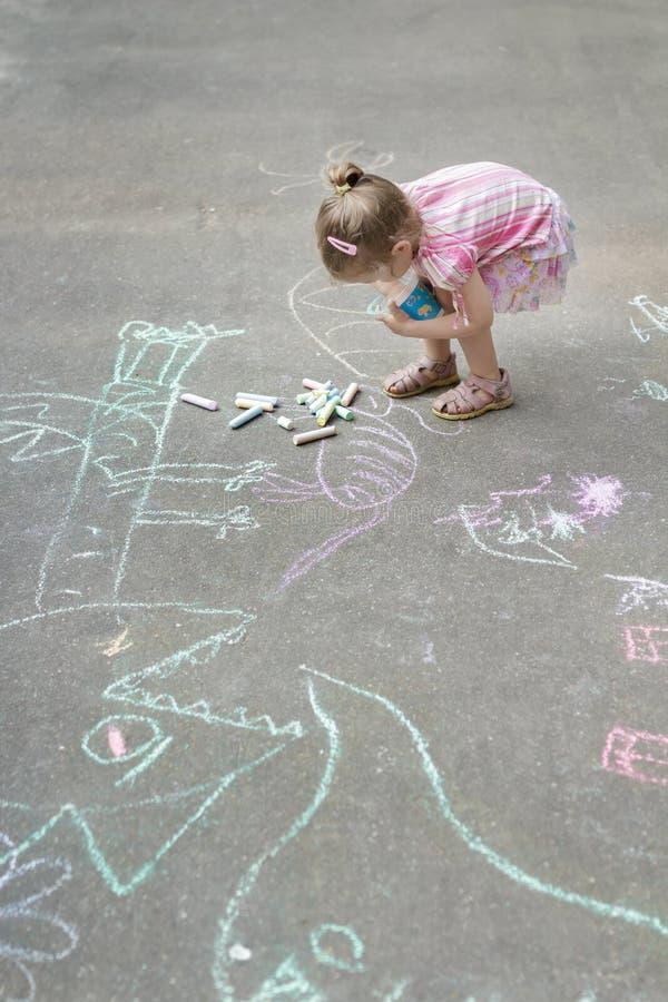 Tir aérien de la petite fille caucasienne marquant à la craie sur la cour de jeu de marelle photo libre de droits