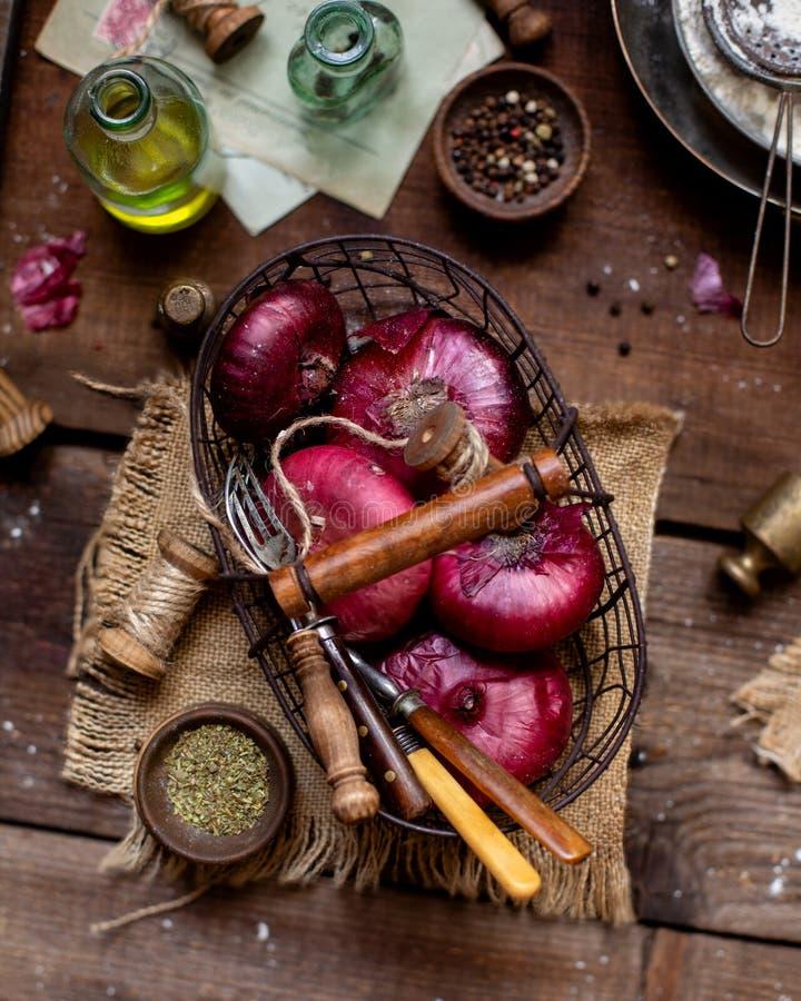 Tir aérien de panier de la position d'oignon rouge sur la table brune en bois avec la toile à sac photos stock