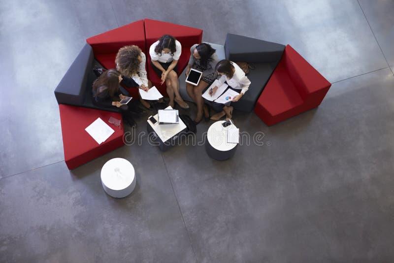 Tir aérien des femmes d'affaires se réunissant dans le lobby du bureau photos stock