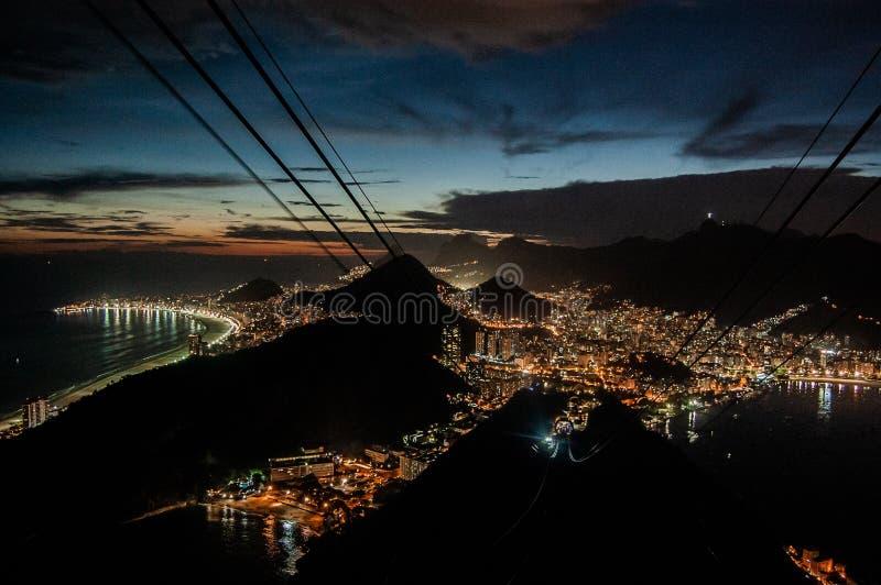 Tir aérien des lumières de bâtiments de ville à la nuit près de la mer et des montagnes photographie stock libre de droits