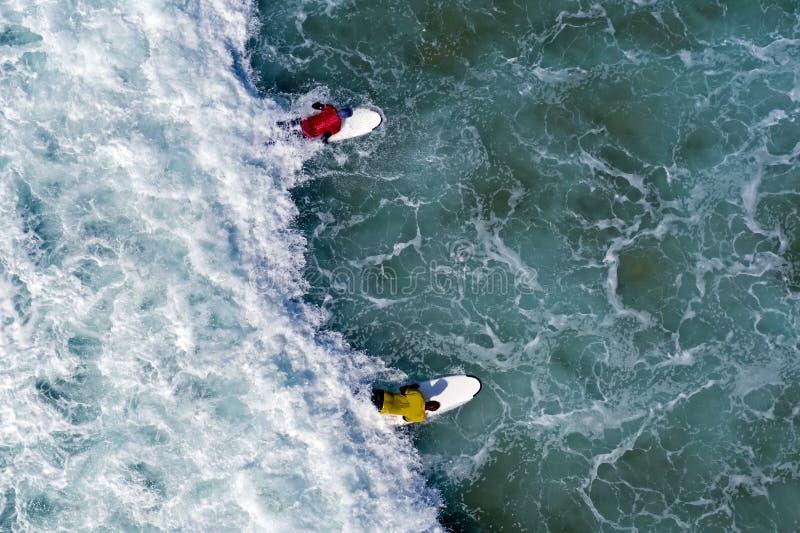 Tir a?rien des surfers essayant d'attraper une vague dans l'oc?an images stock