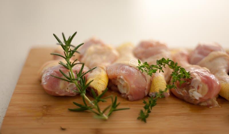 Tir brouillé de poulet sur une planche à découper avec le romarin frais a photographie stock