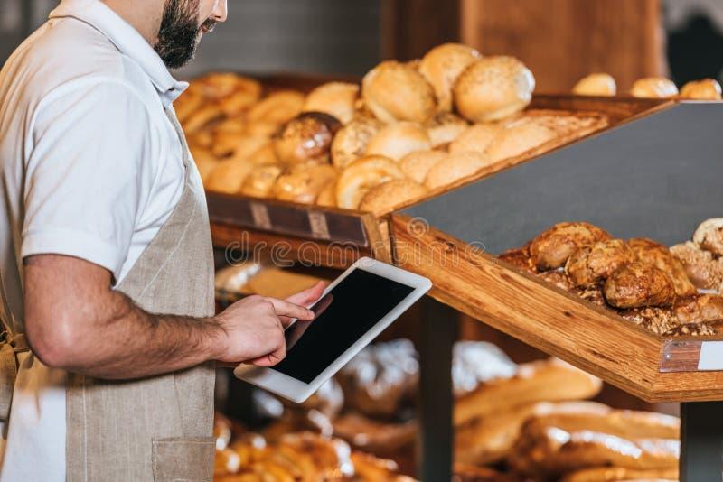 tir cultivé d'employé de magasin dans le tablier utilisant le comprimé avec l'écran vide photo libre de droits