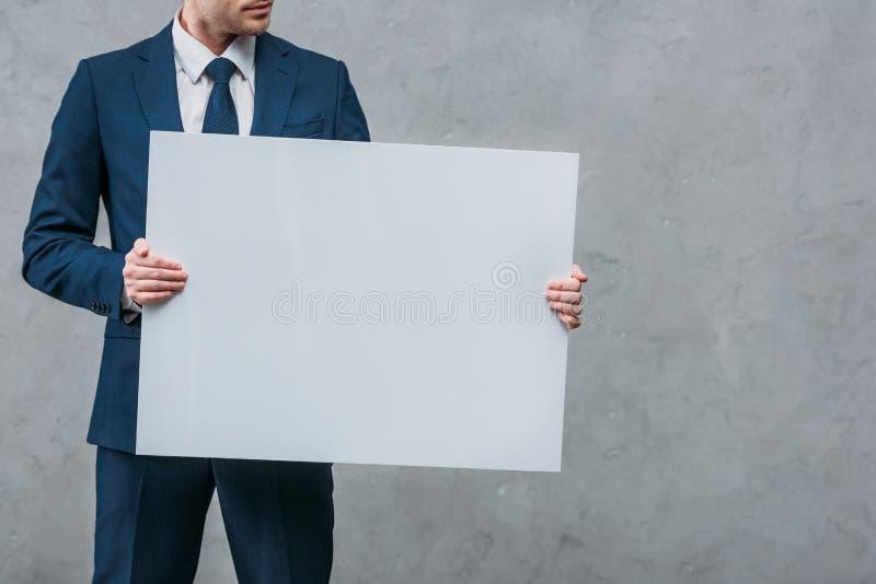tir cultivé d'homme d'affaires tenant le conseil vide devant photo stock