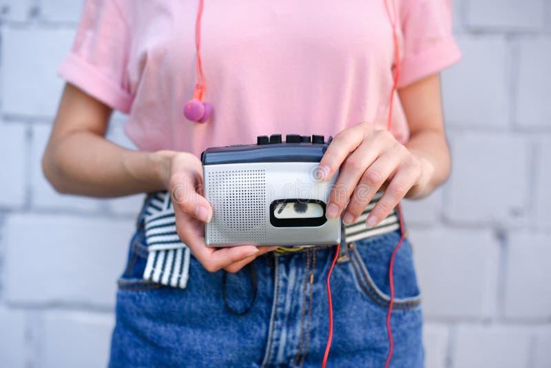 tir cultivé de femme avec des écouteurs tenant le rétro lecteur de cassettes dans des mains contre le blanc photographie stock