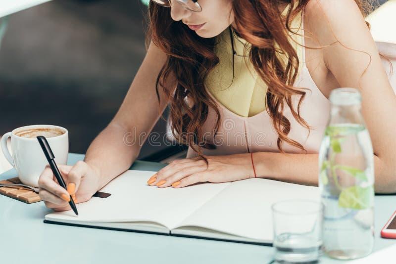 tir cultivé de femme d'affaires faisant des notes dans le carnet à la table images libres de droits