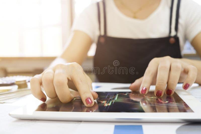 Tir cultivé de femme touchant le graphique de marché boursier sur un dispositif d'écran tactile dans la maison Commerce sur le co photo stock