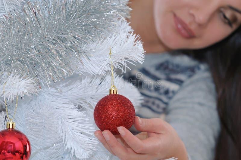Tir cultivé de jeune femme décorant son arbre de Noël au hom image libre de droits