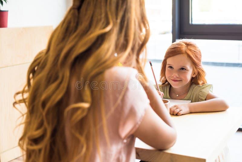 tir cultivé de jeune mère regardant le petit dessin mignon de fille avec le crayon image stock
