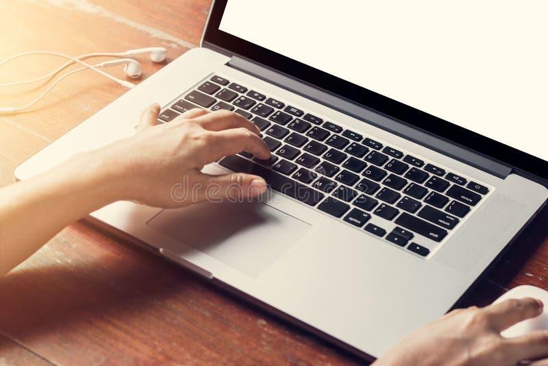 Tir cultivé de l'ordinateur portable de utilisation d'un homme avec l'écran blanc vide photographie stock