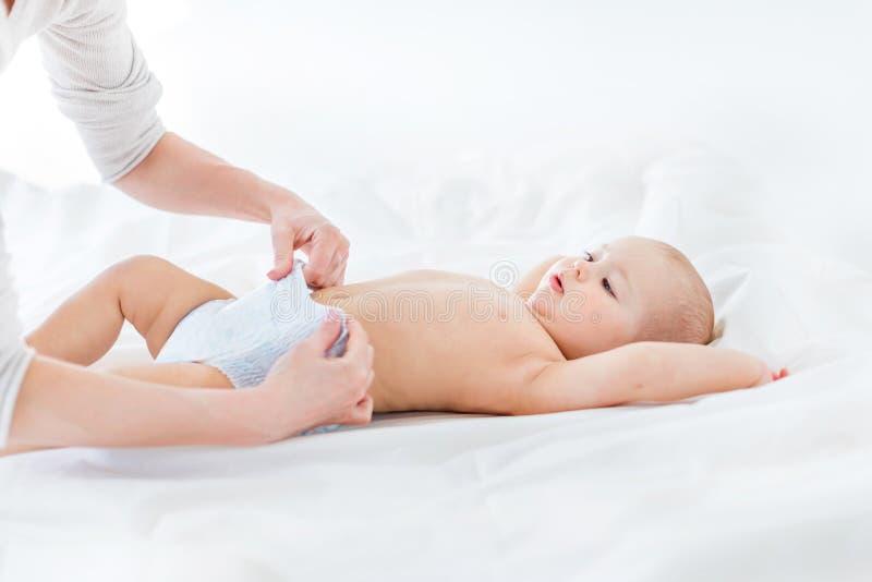 Tir cultivé de la couche-culotte changeante de mère du bébé garçon adorable se trouvant sur le lit photo stock