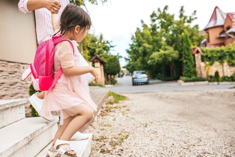 Tir cultivé de la fille de mère et d'élève allant au jardin d'enfants Bonnes relations La petite fille mignonne avec la maman se  photos libres de droits