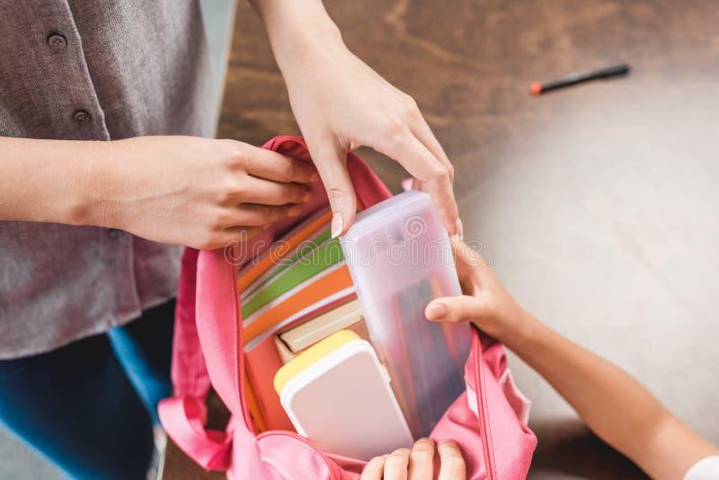 tir cultivé de la mère et de la fille préparant le sac à dos avec des fournitures scolaires images libres de droits