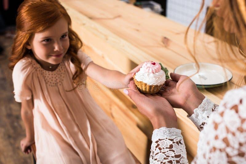 tir cultivé de la mère et de la fille rousse mignonne tenant le petit gâteau image libre de droits