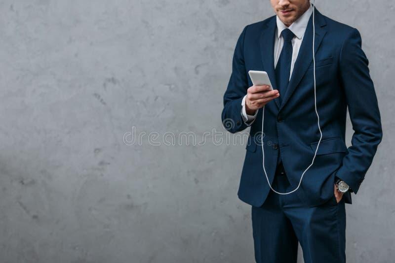 tir cultivé de la musique de écoute d'homme d'affaires avec des écouteurs images stock