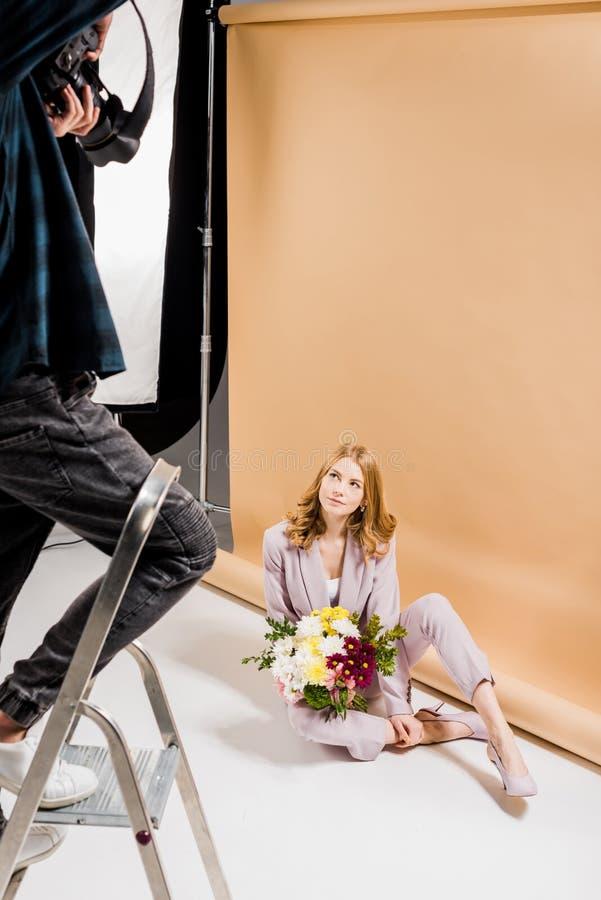 tir cultivé de la position de photographe sur l'échelle d'étape et la belle fille de tir avec des fleurs photographie stock