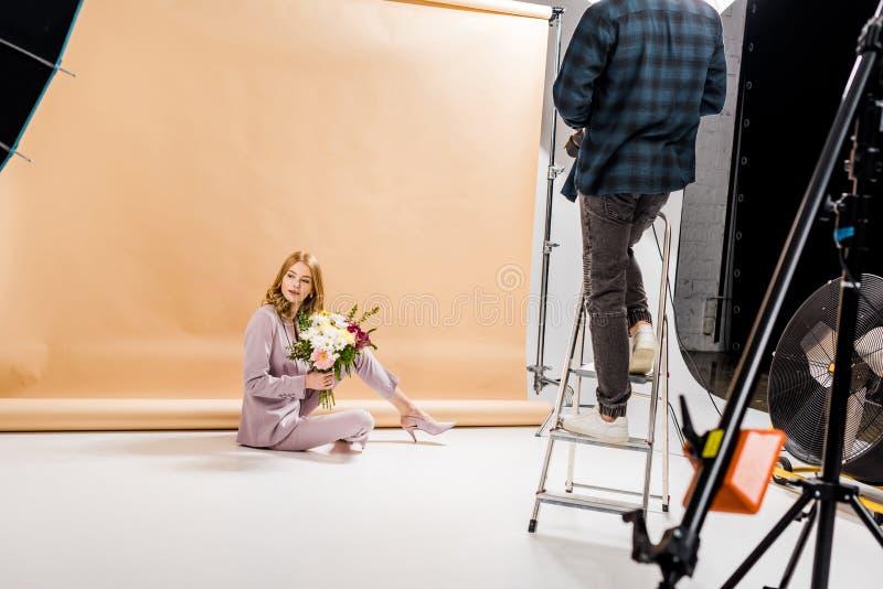 tir cultivé de la position de photographe sur l'échelle d'étape tandis que belle fille posant avec le bouquet des fleurs photographie stock