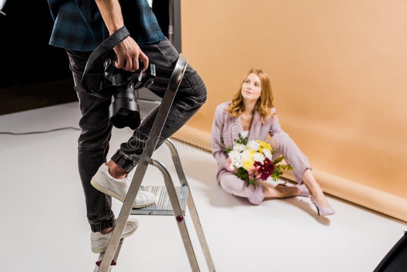 tir cultivé de la position de photographe sur l'échelle d'étape tandis que femme attirante posant avec des fleurs photographie stock