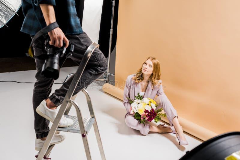 tir cultivé de la position de photographe sur l'échelle d'étape tandis que femme attirante posant avec le bouquet photos libres de droits
