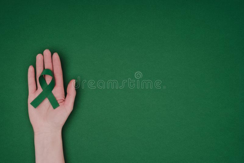 tir cultivé de main femelle avec le ruban vert de conscience pour le ruban vert de conscience pour la scoliose, symbole de santé  image stock