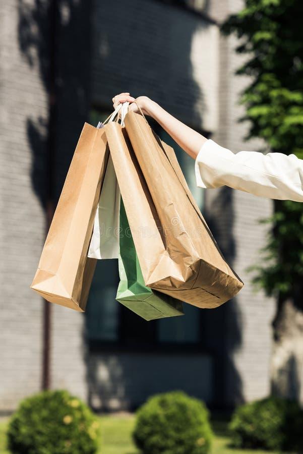 tir cultivé de main femelle tenant des sacs à provisions images stock