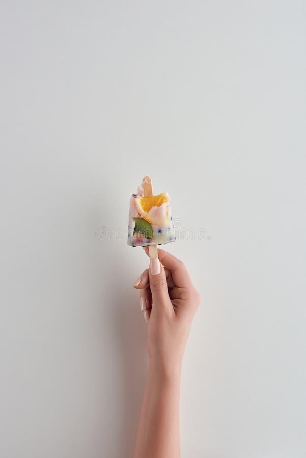 tir cultivé de personne tenant la glace à l'eau fruitée froide fraîche sur le bâton photo stock