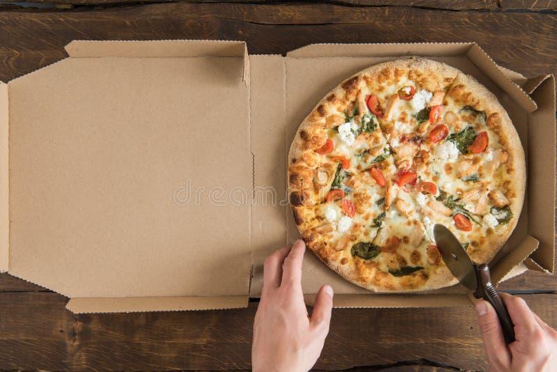 Tir cultivé de personne tenant le coupeur de pizza et coupant la pizza fraîche délicieuse photographie stock