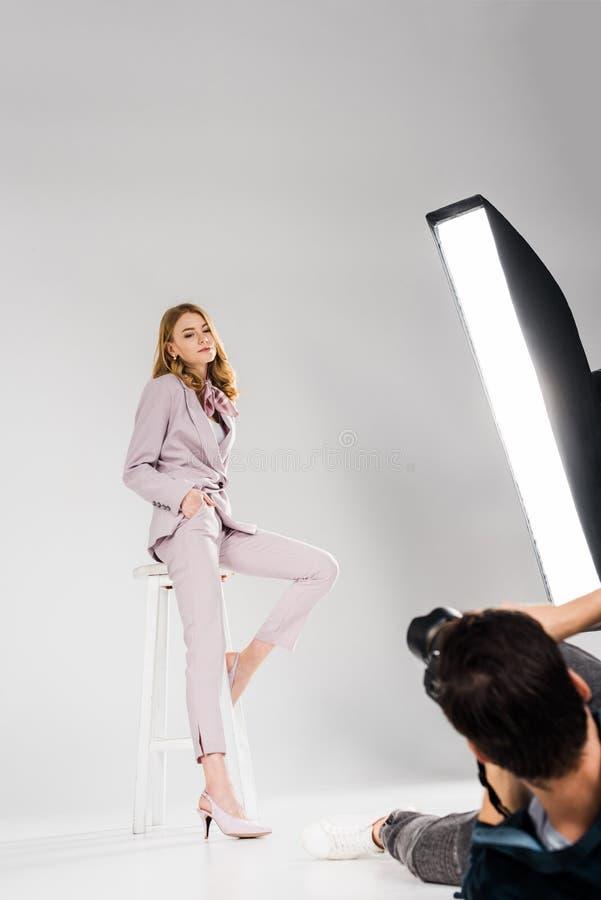 tir cultivé de photographe se trouvant et photographiant la belle jeune femme image stock