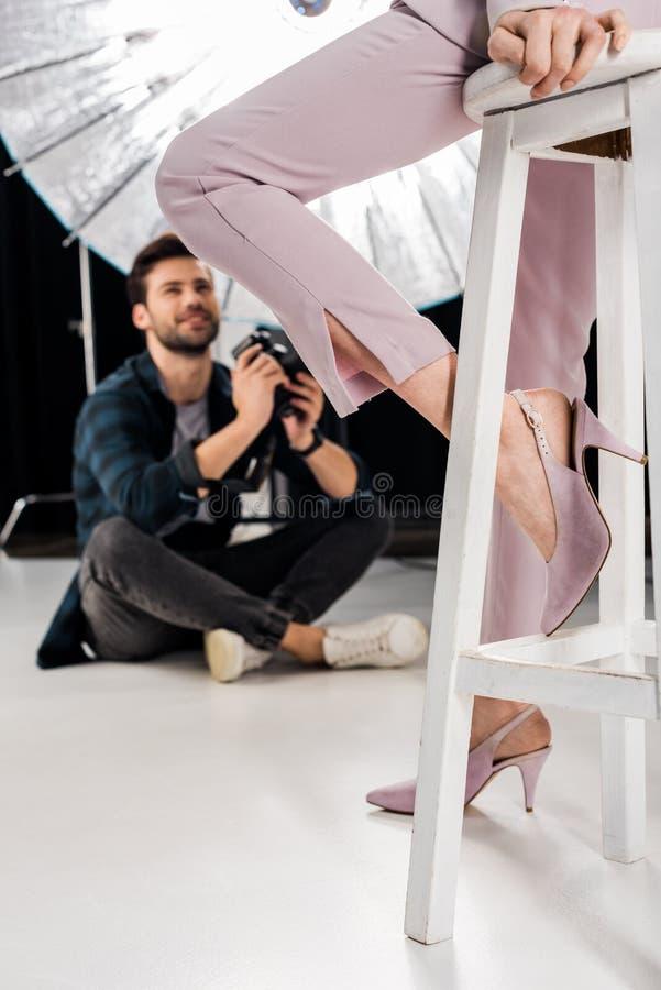 tir cultivé de photographe de sourire reposant et photographiant le modèle femelle élégant images stock