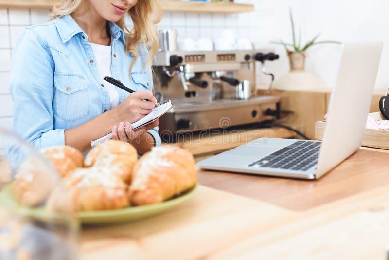 tir cultivé de propriétaire de café prenant des notes photo libre de droits