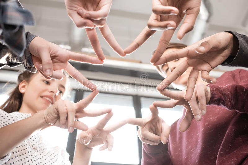Tir cultivé des adolescents faisant des gestes avec des doigts ensemble à l'intérieur photographie stock libre de droits